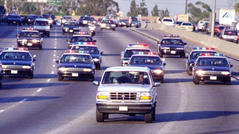 California Highway Patrol officers chase Al Cowling, driving, and O.J. Simpson, in the rear of the white Bronco, on the 91 Freeway just west of the 5 Freeway on June 17, 1994.