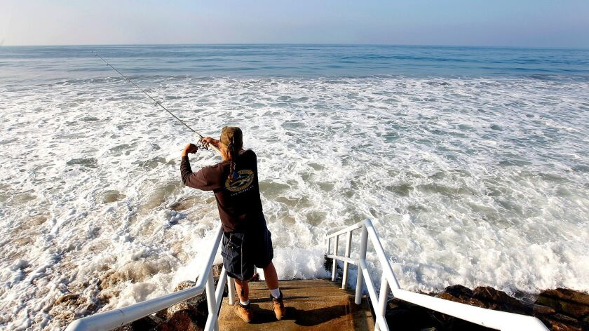 A man fishes off public access stairs during high tide at Broad Beach in Malibu on March 24, 2013. Over several decades that beach has eroded to a dangerous degree.