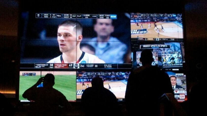Fans watch an NCAA tournament game during college basketball's March Madness, a huge source of revenue for the NCAA, little of which trickles down to players.