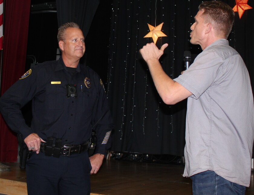 PB Town Council president Brian White (right) gives a warm farewell speech to retiring San Diego police officer Larry Hesselgesser