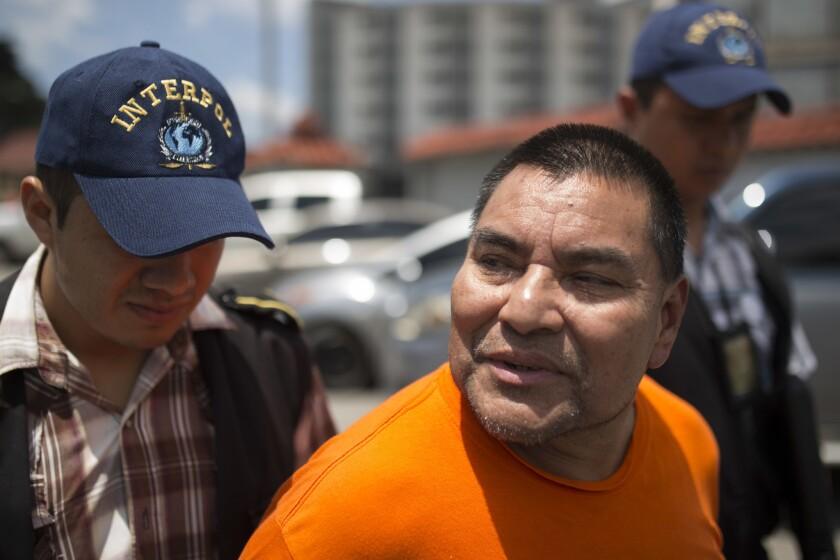 Santos López Alonzo es escoltado por agentes de la Interpol luego de aterrizar en la base de la Fuerza Aérea en Ciudad de Guatemala. López Alonzo, un ex soldado guatemalteco, es sospechoso de ayudar a efecturar la masacre de más de 160 personas en 1982 durante la guerra civil de su país, y fue deportado por los Estados Unidos. (AP Foto/Luis Soto)