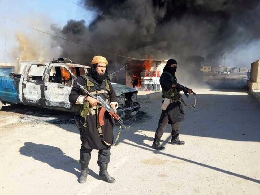 """This image posted on a militant website, which is consistent with other reporting, shows Shakir Waheib, a senior member of the Islamic State of Iraq and Syria, left, next to a burning police vehicle in Iraq's Anbar Province. Al Qaeda has declared publicly that it has no link to the group known as ISIS, which is waging a brutal guerrilla war in both Iraq and Syria. The Islamic State is """"not a branch of Al Qaeda,¿ has no ¿organizational relationship¿ with Al Qaeda, declared a blunt statement issued by Al Qaeda's Pakistan-based central command."""
