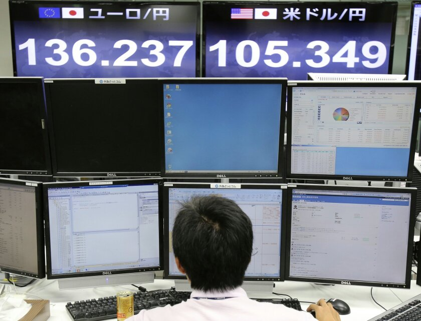 A foreign exchange company money trader works as screens show the current exchange rate of Japanese yen against U.S. dollar, top right, and euro, top left, in Tokyo, Friday, Sept. 5, 2014. The U.S. dollar rose to around 105.70 yen, the highest since October 2008, on Friday morning. (AP Photo/Koji Sasahara)