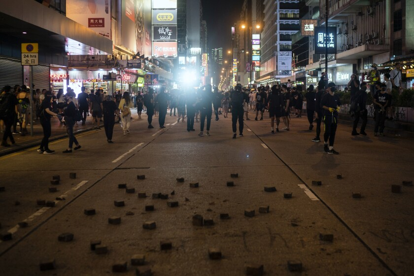Riot police chase protesters near a demonstration in Hong Kong, Monday, Oct. 7, 2019. Tens of thousands of masked protesters marched defiantly in the city center Sunday, but the peaceful rallies quickly degenerated into chaos at several locations as hard-liners again lobbed gasoline bombs, started fires and trashed subway stations and China-linked banks and shops.(AP Photo/Felipe Dana)