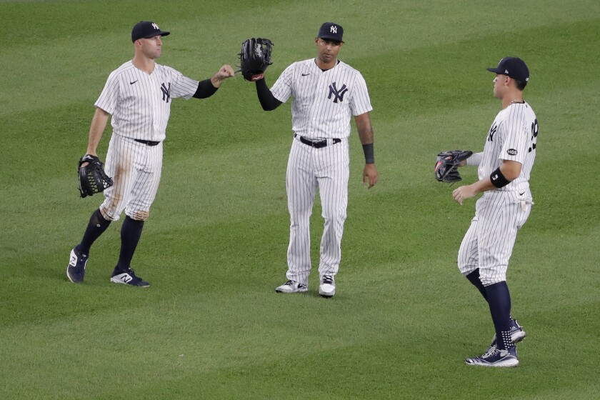 New York Yankees outfielders Brett Gardner, left, Aaron Hicks, center and Aaron Judge celebrate after the baseball game against the Boston Red Sox at Yankee Stadium, Friday, July 31, 2020, in New York. The Yankees defeated the Red Sox 5-1. (AP Photo/Seth Wenig)