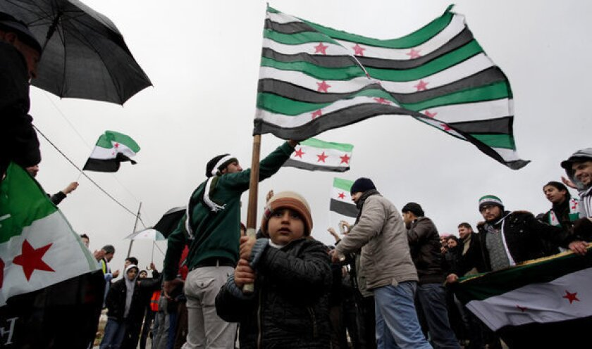 Syrians, many of them refugees from the 21-month-old uprising in their homeland, chant denunciations of Syrian President Bashar Assad outside the Syrian Embassy in Amman, Jordan.