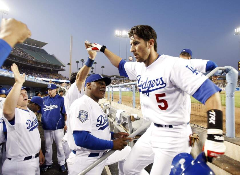 Los Angeles Dodgers' Nomar Garciaparra (5) is congratulated in the dugout after hitting a two-run home run against Atlanta Braves pitcher Jorge Campillo to score teammate James Loney during the fifth inning of a baseball game at Dodger Stadium in Los Angeles, Monday, July 7, 2008.