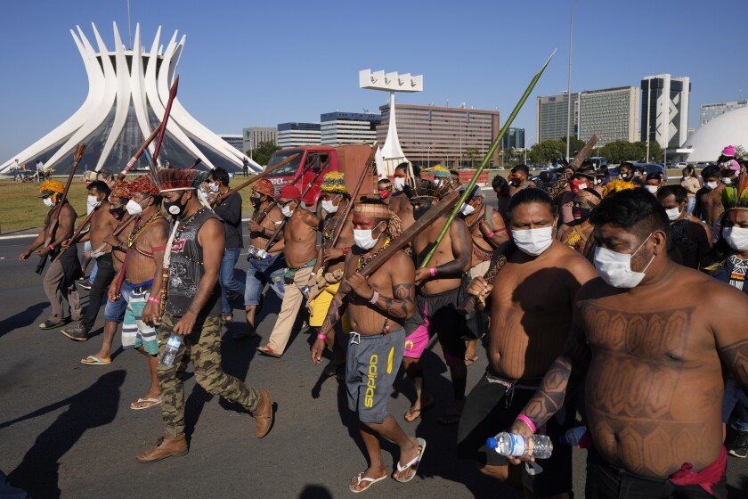 Indigenous march past the Cathedral in Brasilia, Brazil, Wednesday, June 23, 2021. Indigenous activists have traveled to the capital to demand government action to halt illegal mining and logging on their land and oppose a proposed bill they say would limit recognition of tribal lands. (AP Photo/Ricardo Mazalan)