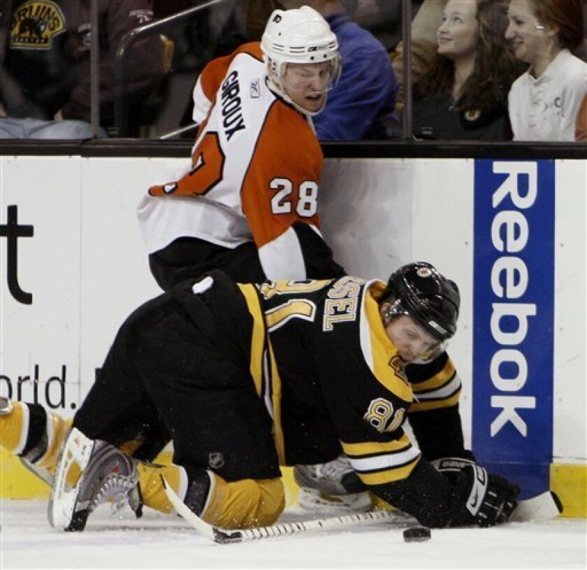 Boston Bruins' Phil Kessel (81) eyes a loose puck with Philadelphia Flyers' Claude Giroux during the second period of a hockey game in Boston, Saturday, Feb. 7, 2009. (AP Photo/Winslow Townson)