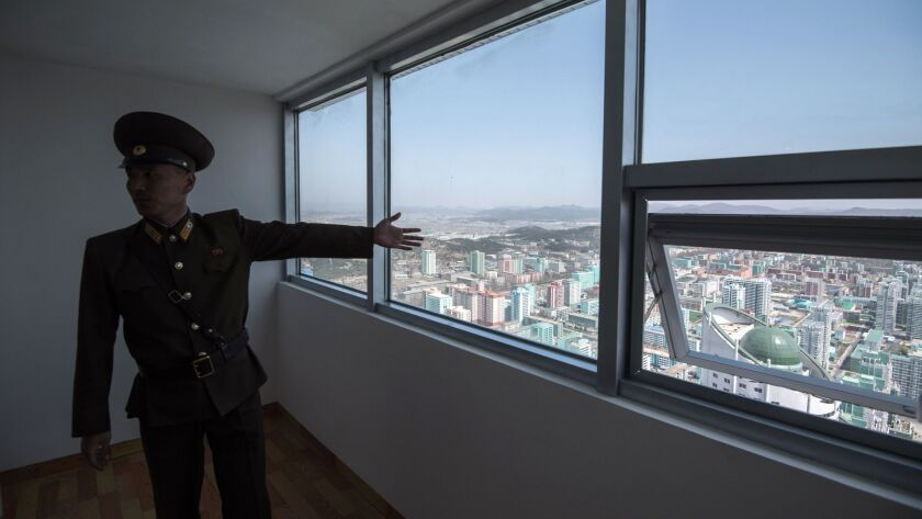 A Korean People's Army soldier shows off an apartment in the Ryomyong Street housing development in