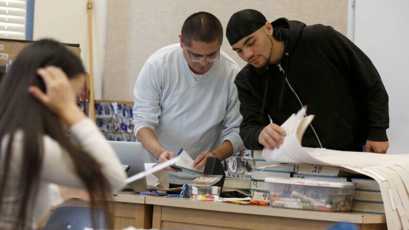 Teacher Joel Wing and Desmond Pueyrredon, 17, right, go over paperwork in his Oakland classroom.