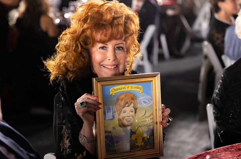 Dianne Bashor, honored with the late Father Joe Carroll and David Macolm at the Scouts BSA gala, holds a Steve Breen drawing.