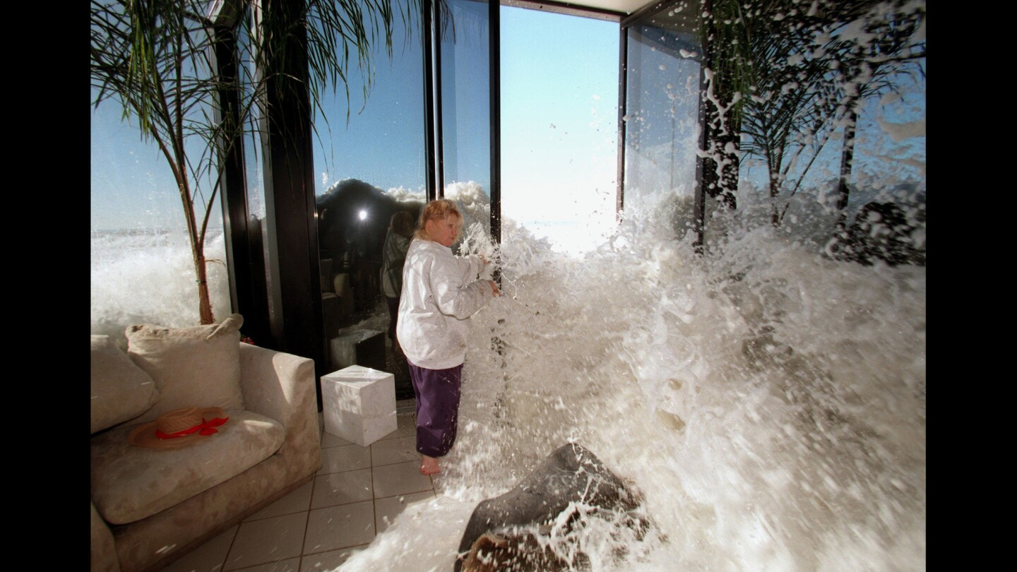 Marilyn Lane tries to shut a door as a wave rushes into her Solimar Beach home during a January 1998 storm.