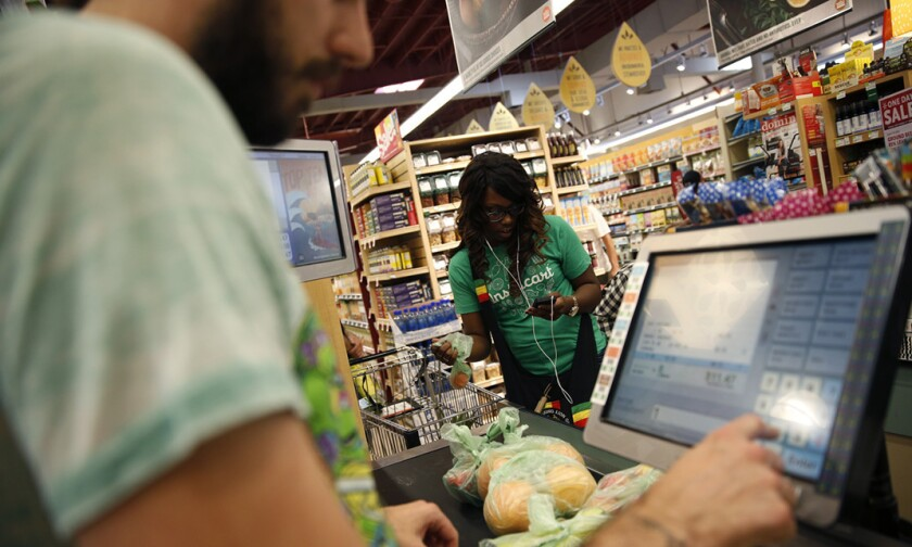 Whole Foods cashier Jason Ellsworth rings up groceries as Instacart shopper Kara Pete double-checks items ordered by a customer.