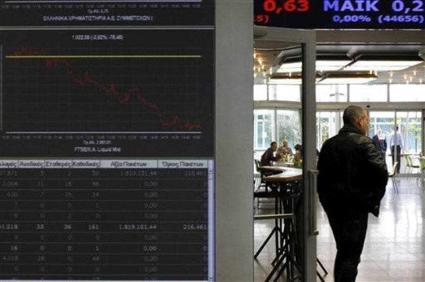 A man walks past a screen showing falling stocks at the Athens Stock Exchange in Greece on Monday, Feb. 8, 2010. The Greek exchange remained locked in a bear session Monday, with shares falling 3.7 percent in afternoon trading, even as European stocks rebounded on hopes Greece won't be allowed to default on its crushing debt load. The center-left government is putting the final touches to draft tax reforms meant to boost ailing state coffers, which saw a 12.7 percent budget shortfall last year. (AP Photo/Petros Giannakouris)