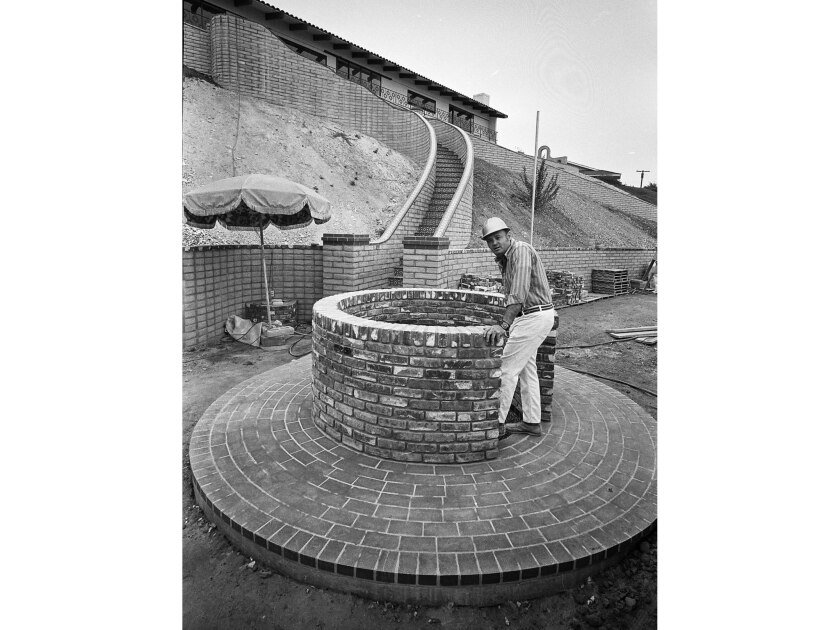 ESCAPE' ROUTE--Bill Bounds at the entrance of spiral staircase leading to his smog-alert chamber at