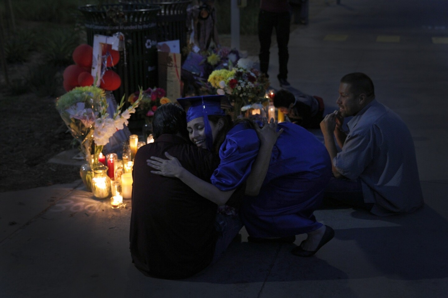 Patty Medina, who graduated from Santa Monica College on Tuesday, comforts Rafael Torres, left, and Gabriel Torres, sons of Margarita Gomez, who was gunned down near the campus library Friday. The fatal shootings have altered the crime picture in Santa Monica.