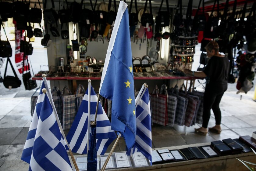 """A woman adjusts items beside the flags of European Union flag, center top, and Greece, outside a kiosk in Piraeus, near Athens, Greece, on Sunday, June 14, 2015.  A government official says Greek Prime Minister Alexis Tsipras has told senior aides to """"forget about elections or a referendum,"""" whatev"""