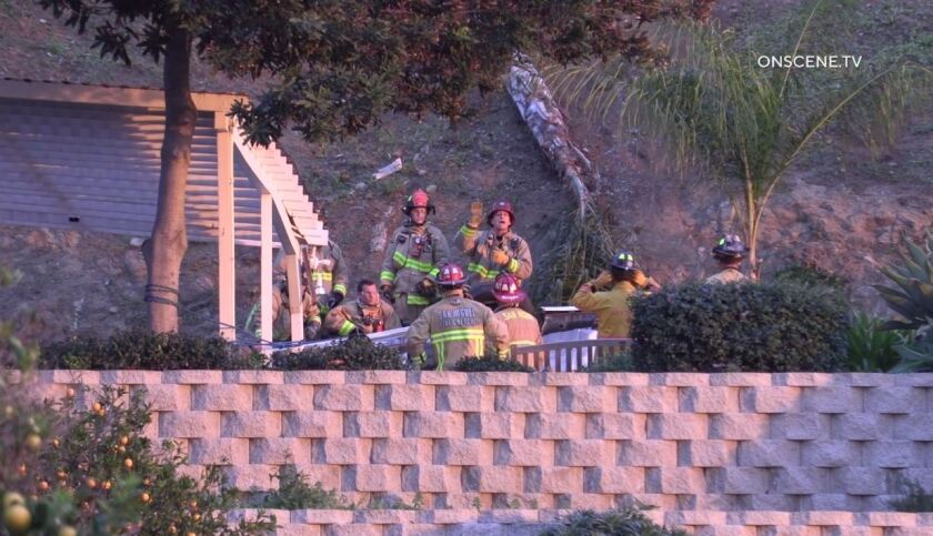 Emergency crews from San Miguel Fire & Rescue surround an overturned car that landed in the back patio area of a home on La Cruz Place.