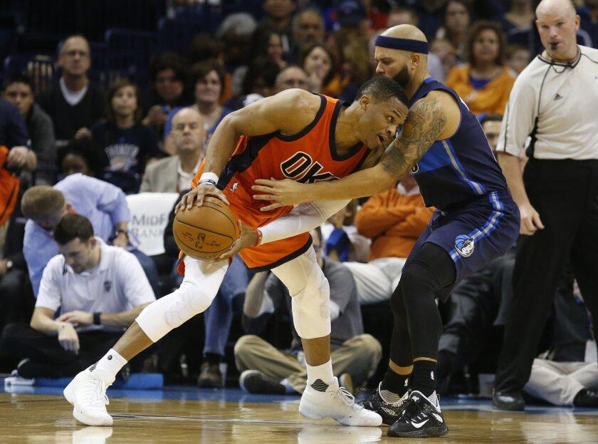 Oklahoma City Thunder guard Russell Westbrook, left, drives around Dallas Mavericks guard Deron Williams during the second quarter of an NBA basketball game in Oklahoma City, Sunday, Nov. 22, 2015. (AP Photo/Sue Ogrocki)
