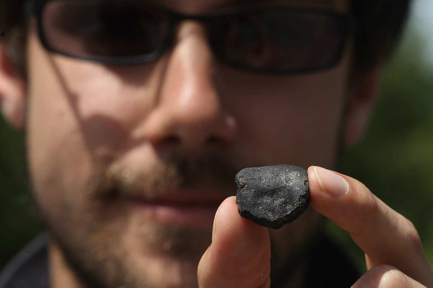 Jason Utas, a geology student at UC Berkeley, holds a 7.5-gram fragment of a meteorite called CM chondrite he found Friday in Coloma, Calif. He was among the many people who descended into the area following a fireball on April 22. Utas found the fragment in the David Moore Nature Area off Highway 49, just west of Coloma. Scientists used weather radar to track the movements of the object and predicted it fell near Coloma. The meteorite is a rare class that contains water and carbon compounds that are similar to those responsible for producing life on Earth. It is in this location that gold was first discovered in 1848.
