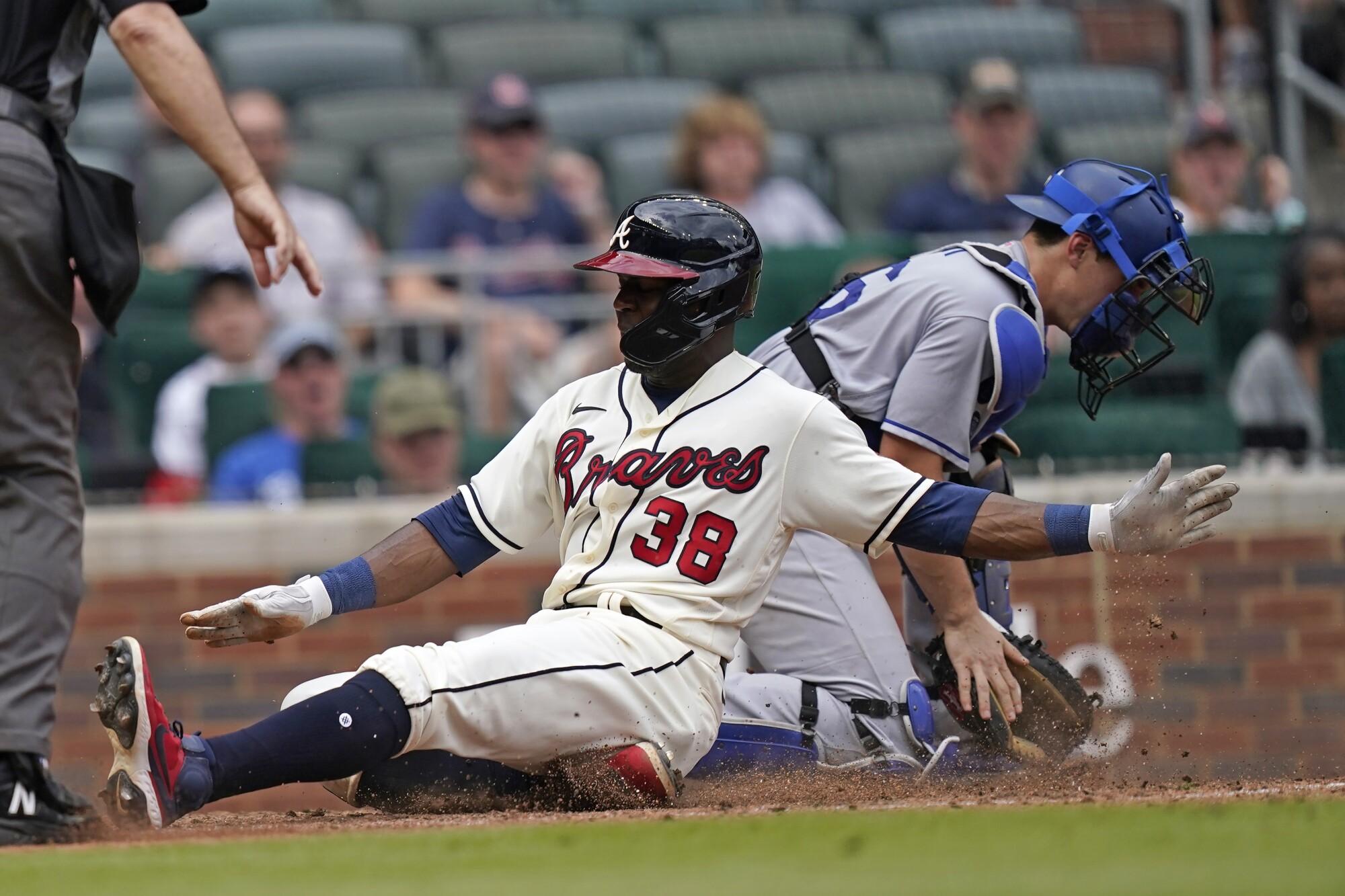 Atlanta's Guillermo Heredia scores next to Dodgers catcher Will Smith.