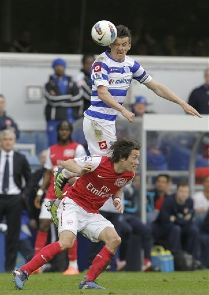 Queens Park Rangers' Joey Barton, top, climbs above Arsenal's Tomas Rosicky during their English Premier League soccer match at Loftus Road stadium, London, Saturday, March 31, 2012. (AP Photo/Sang Tan)