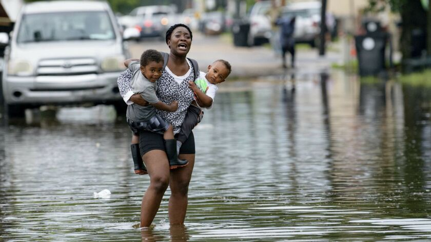 Terrian Jones reacts as she feels something moving in the water at her feet as she carries Drew and Chance Furlough to their mother on Belfast Street in New Orleans during flooding Wednesday.