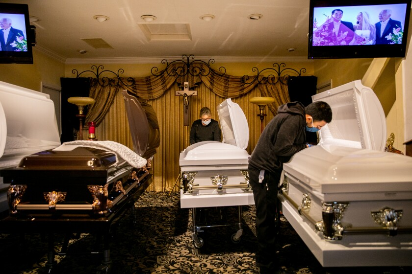 Sammy Deras (right), a funeral attendant, and Kristy Oliver, an embalmer and funeral director, make final preparations.