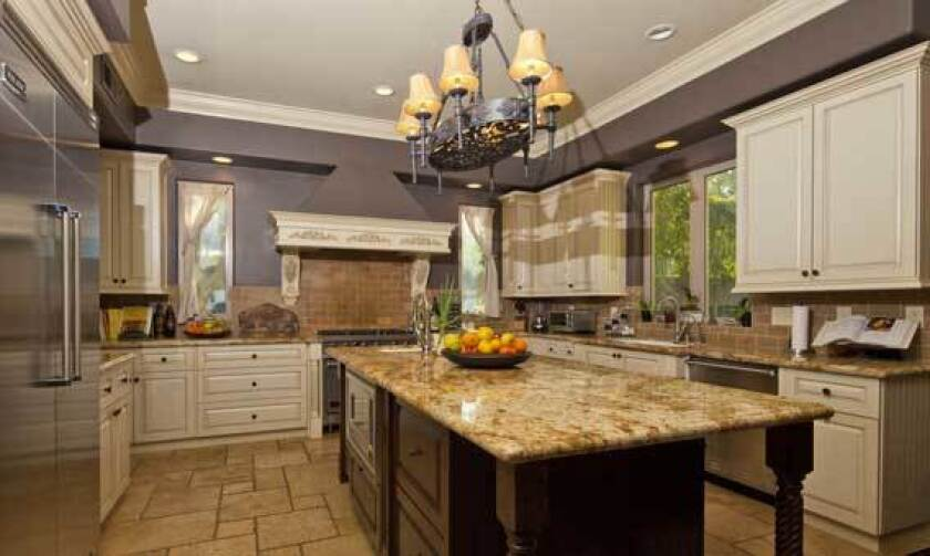 The kitchen in Billy Howerdel's house has a granite-topped island and stainless appliances.
