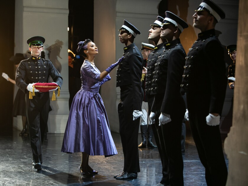 Goodbye track jacket, hello shimmering dress: The view from the wings as the Queen greets the guards.