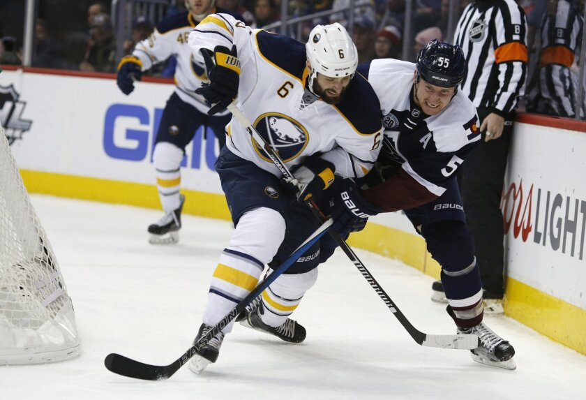 Buffalo Sabres defenseman Mike Weber, left, checks Colorado Avalanche left wing Cody McLeod as they pursue the puck behind the net during the third period of an NHL hockey game Wednesday, Jan. 20, 2016, in Denver. Colorado won 2-1. (AP Photo/David Zalubowski)
