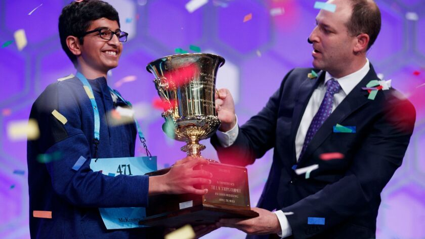 Scripps National Spelling Bee winner Karthik Nemmani receives the championship trophy from Adam Symson, president and CEO of the E.W. Scripps Co.