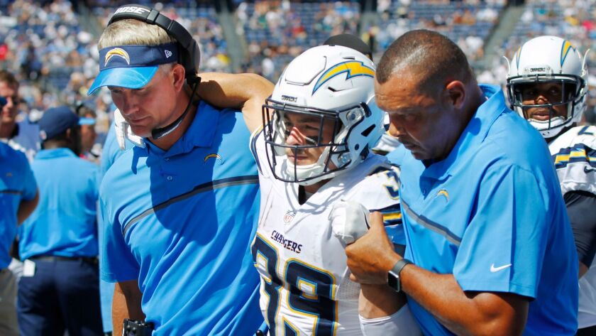 Chargers Danny Woodhead is helped off the field by Mike McCoy and James Collins in the 1st quarter after getting injured on a play.