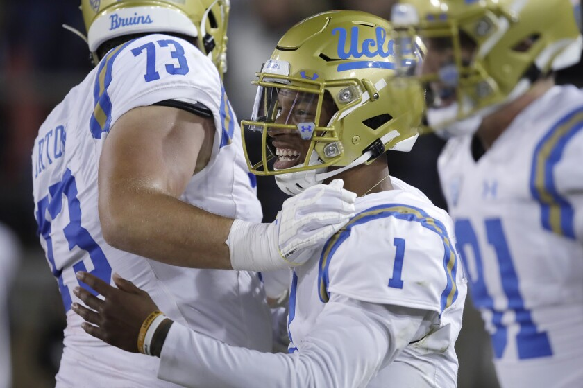 UCLA quarterback Dorian Thompson-Robinson, right, celebrates with teammate Jake Burton after scoring a touchdown against Stanford in the first half Thursday.
