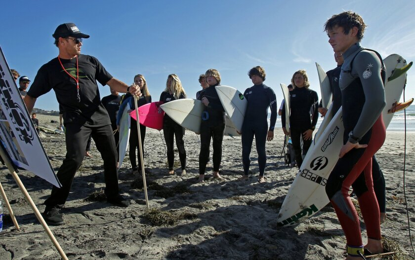 """Professional surfer Taylor Knox gave a surfing clinic to local high school surfers at Ponto Beach in Carlsbad on Wednesday, March 21, 2012. During the """"School of Hard Knox"""", Knox gave the north county surfers tips on using their rails before they went out, then critiqued them as they surfed."""
