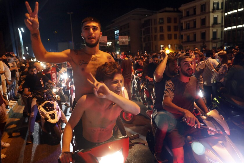 Anti-government protesters flash the victory sign as they block a road during a protest against the political leadership they blame for the economic and financial crisis, in Beirut, Lebanon, Thursday, June 11, 2020. (AP Photo / Hussein Malla)