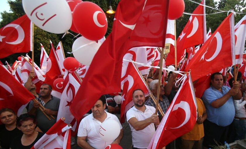 Turkish Cypriot demonstrators wave Turkish and Turkish Cypriot flags.