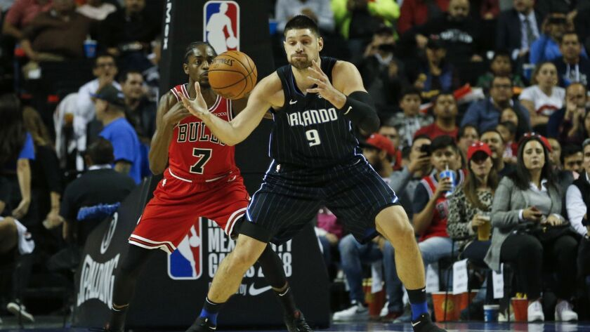 Orlando Magic's Nikola Vucevic, right, is defended by Chicago Bulls' Justin Holiday in the first hal