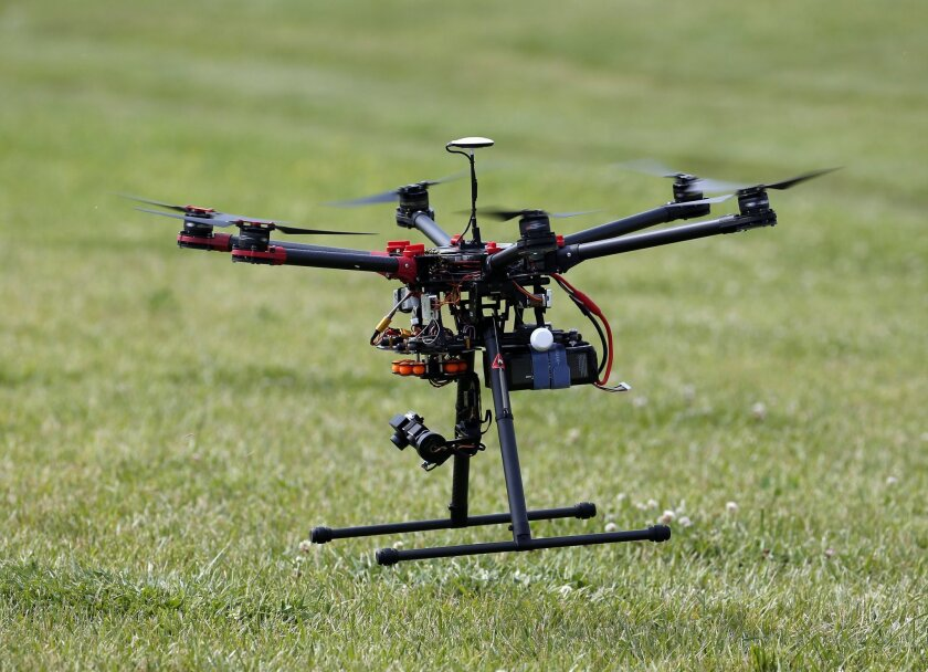 In this photo taken June 11, 2015, a hexacopter drone is flown during a demonstration in Cordova, Md. An aviation industry task force plans to recommend Friday that operators be required to register drones weighing as little as a half of a pound, a threshold that could capture some remote-controlled toys, industry officials said. (AP Photo/Alex Brandon)