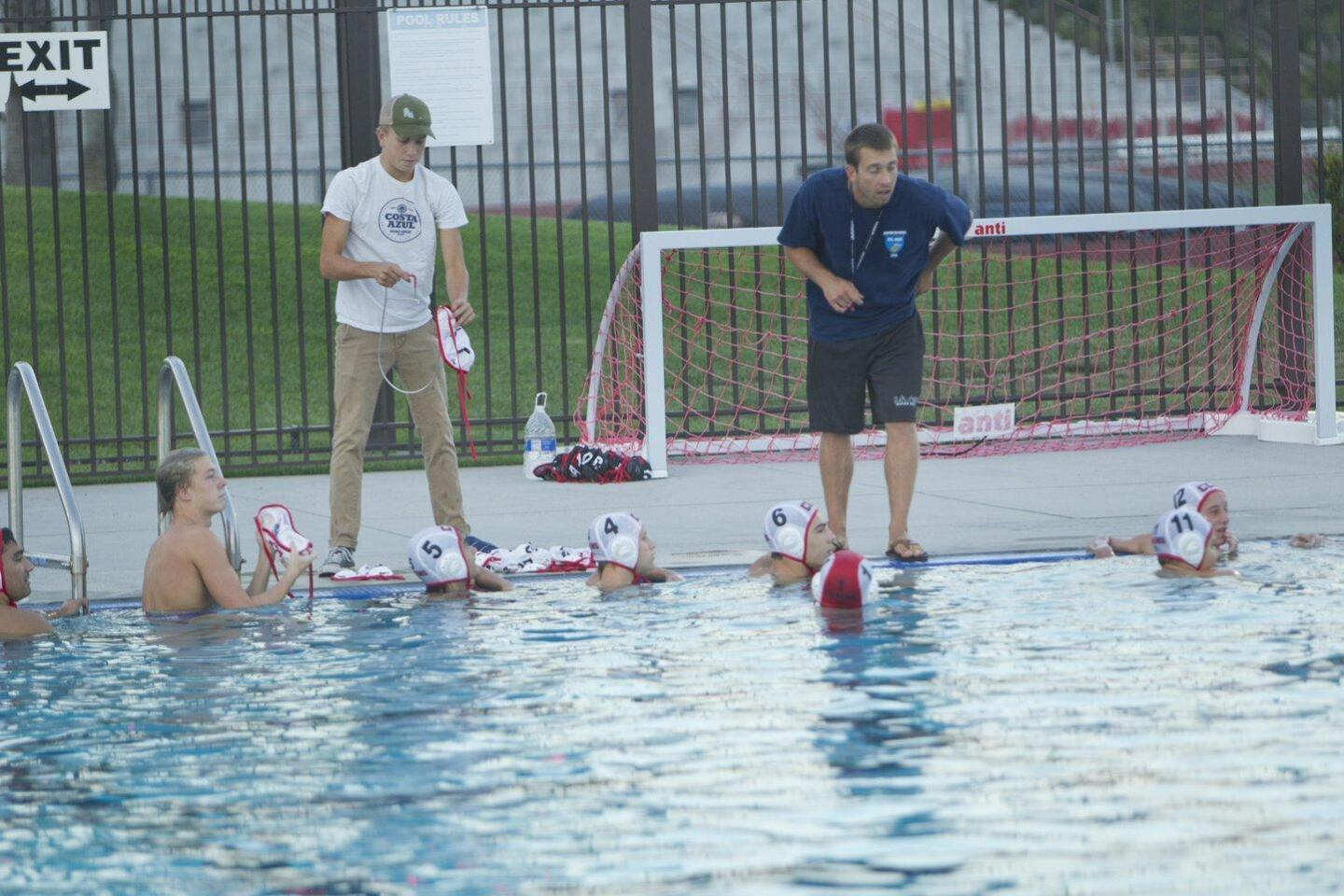 CCA water polo coach Tyler Ormsby (in blue) talks with his varsity team