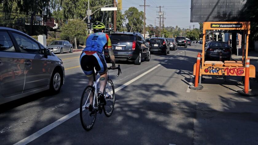 A bicyclist rides alongside traffic on Rowena Avenue.