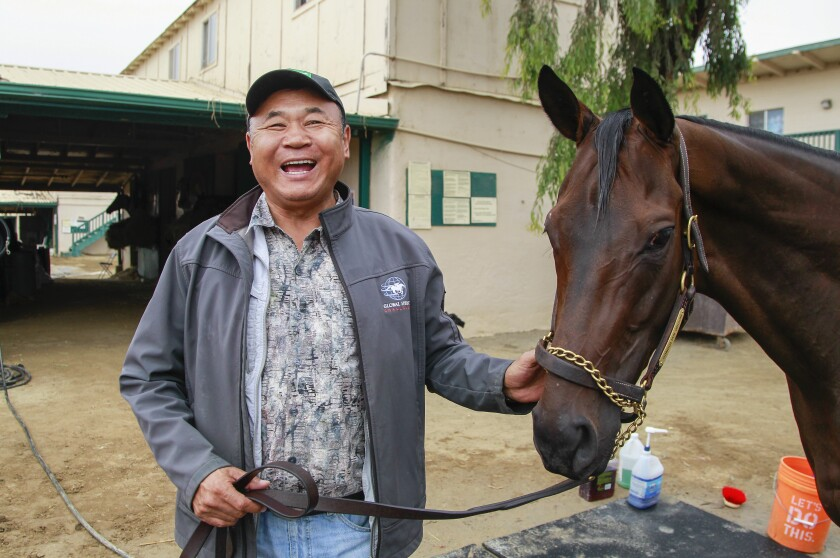 Horse trainer Enebish Ganbat, who is from Mongolia, has a laugh as he poses for photos with Mongolian Groom on August 14, 2019 in San Diego, California.