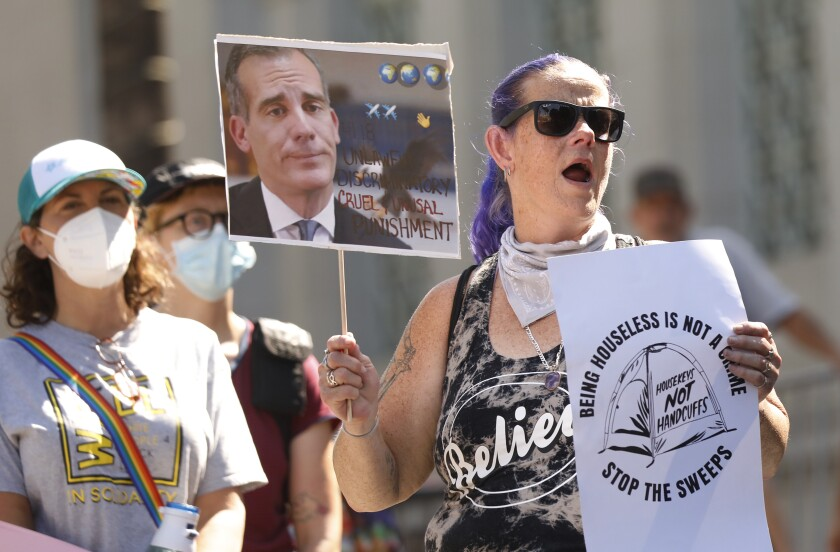 A woman holds signs and stands next to other people