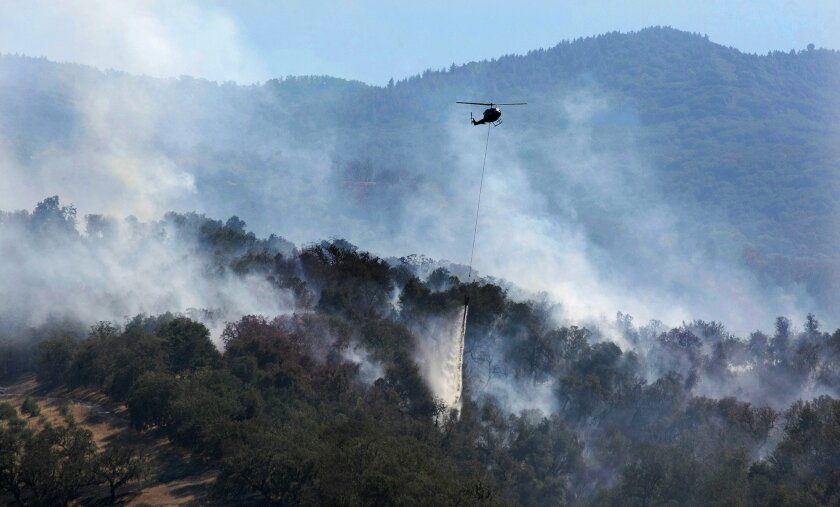 A helicopter makes a water drop on a wildfire hotspot on Sept. 20 in Carmel Valley, Calif.