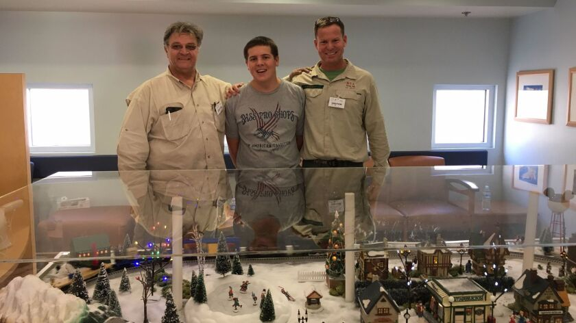 John Stojic, Philippe Naviaux and his father, Jacques Naviaux, pose with the finished winter village railroad display at Rady Children's Hospital.