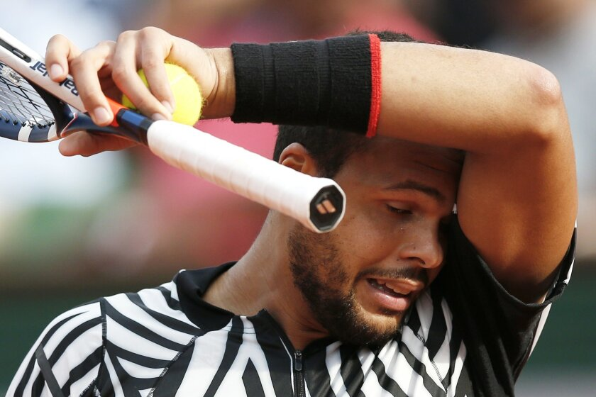 France's Jo-Wilfried Tsonga wipes his face as he plays Latvia's Ernests Gulbis during their third round match of the French Open tennis tournament at the Roland Garros stadium, Saturday, May 28, 2016 in Paris.  (AP Photo/Christophe Ena)
