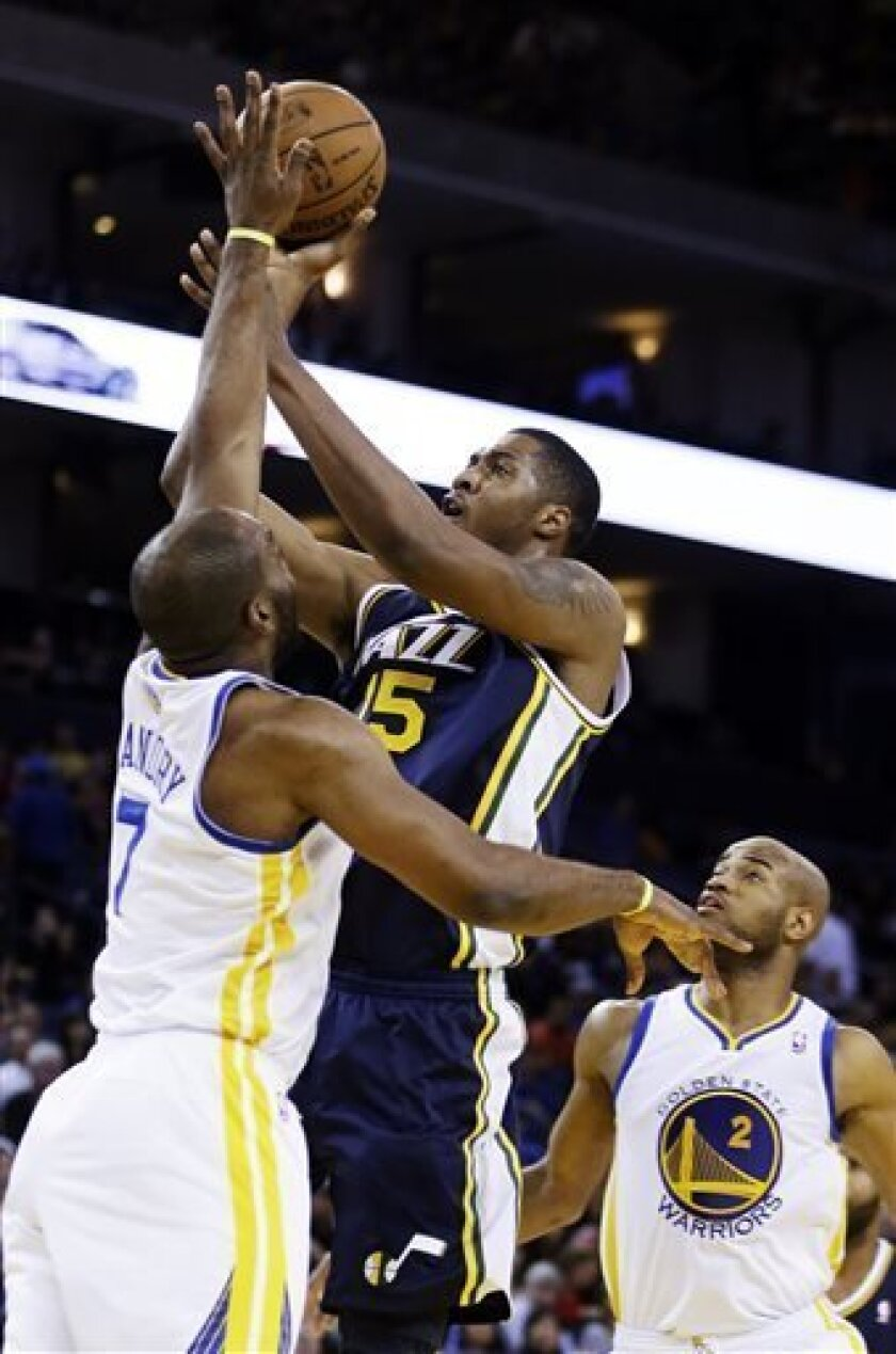 Utah Jazz's Derrick Favors (15) shoots over Golden State Warriors' Carl Landry during the first half of an NBA basketball game, Sunday, April 7, 2013, in Oakland, Calif. (AP Photo/Ben Margot)