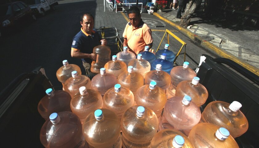 A vendor (right) prepares to fill his bicycle cart with 18-liter jugs of bottled water to sell to owners of street food stalls in Mexico City.