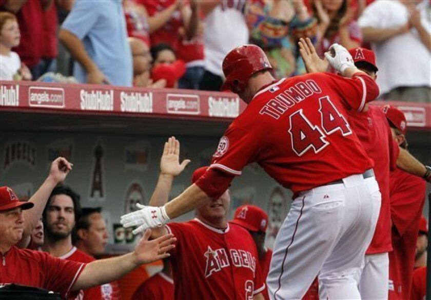 Los Angeles Angels Mark Trumbo is congratulated after hitting a two-run home run in the first inning of a baseball game against the Seattle Mariners in Anaheim, Calif. on Sept. 5, 2011. (AP Photo/Christine Cotter)